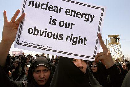 """estudante iraniano com cartaz escrito """"energia nuclear é nosso direito óbvio"""""""