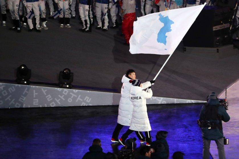 Dois atletas caminham juntos sob a bandeira da unificação coreana